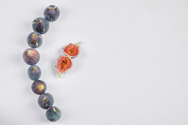 Całe figi i plastry figowe na białym tle.