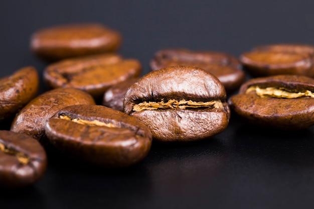 Całe i aromatyczne ziarna kawy porozrzucane w chaotycznym porządku, palone i gotowe do użycia do zrobienia ziaren kawy