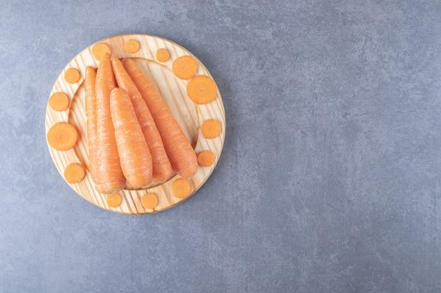 Całe i krojone marchewki w drewnianym talerzu, na marmurowym tle.