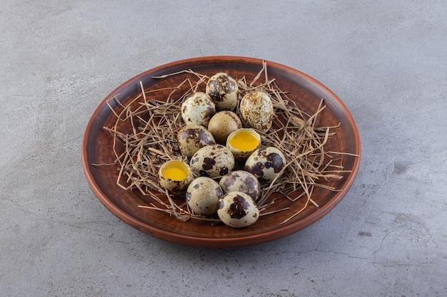 Całe i łamane surowe jaja przepiórcze na talerzu umieszczonym na kamiennym stole.