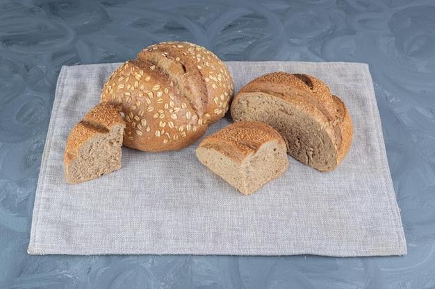 Całe i pokrojone bochenki chleba zawinięte na ręczniku na marmurowym stole.
