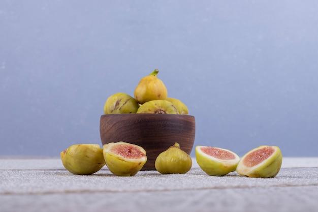 Całe i pokrojone figi w drewnianej misce i pośrodku na białym stole