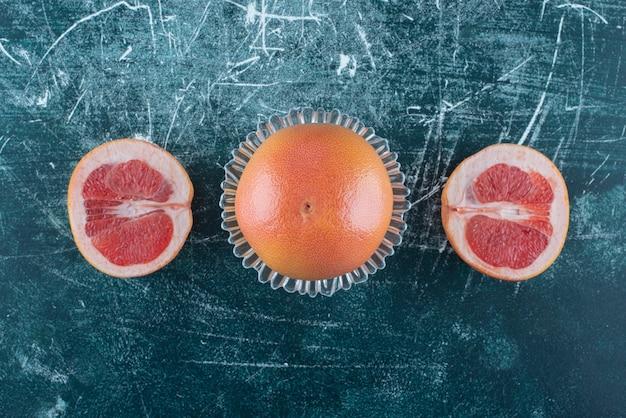 Całe i pokrojone grejpfruty na marmurowym stole.