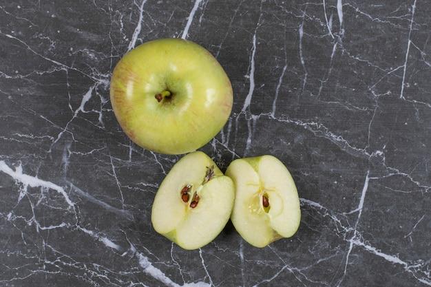 Całe i pokrojone jabłka na marmurze.