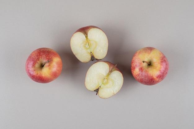 Całe i pokrojone jabłka wystawione na marmurze
