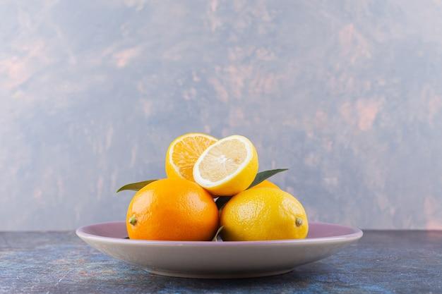 Całe i pokrojone owoce cytryny z liśćmi umieszczone na kamiennym stole.