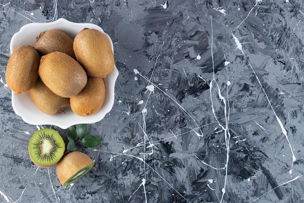 Całe i pokrojone owoce kiwi w szklanej desce.
