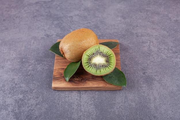 Całe i pokrojone owoce kiwi z liśćmi ułożonymi na kamieniu.