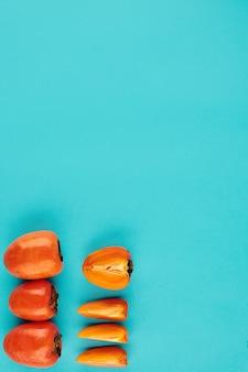 Całe i pokrojone owoce persimmon na brigh niebieskim tle, zdrowe odżywianie i koncepcja przekąsek