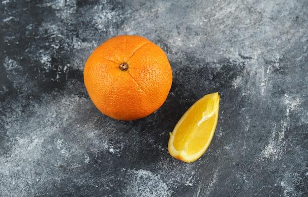 Całe i pokrojone pomarańcze na marmurowym stole.