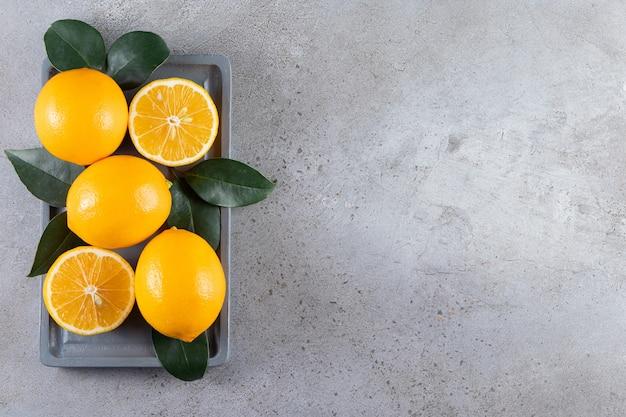 Całe i pokrojone pomarańcze z liśćmi ułożonymi na pokładzie.