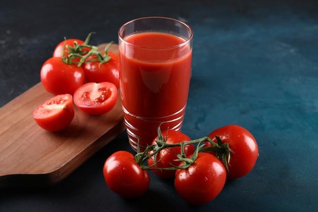 Całe i pokrojone pomidory i szklanka soku pomidorowego.