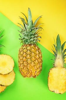 Całe i pokrojone świeże ananasy na kolorowym tle