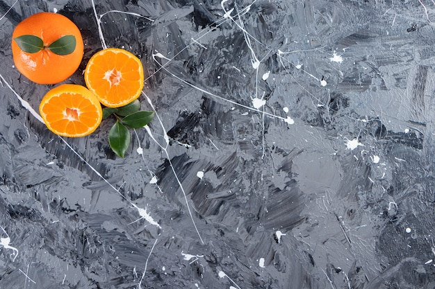 Całe i pokrojone świeże pomarańczowe owoce z liśćmi ułożone na marmurowym stole.