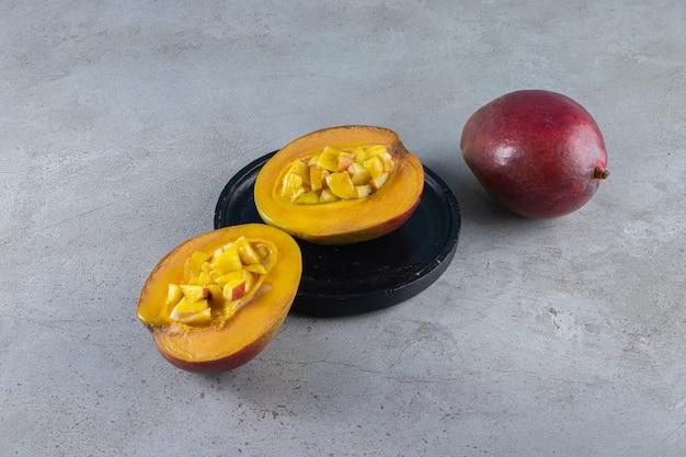 Całe i pokrojone w plasterki dojrzałe mango umieszczone na kamiennej powierzchni.
