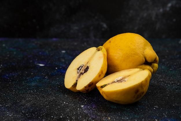 Całe i pokrojone w plasterki dojrzałe owoce pigwy umieszczone na ciemnym stole.