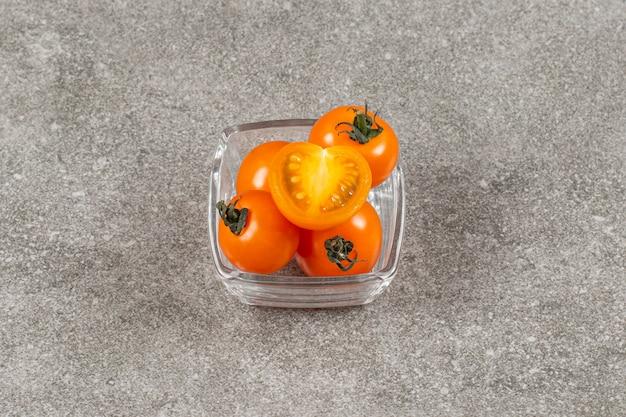 Całe i pokrojone żółte pomidory koktajlowe.