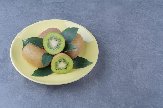 Całe i pół owoce kiwi na talerzu na marmurowym stole.