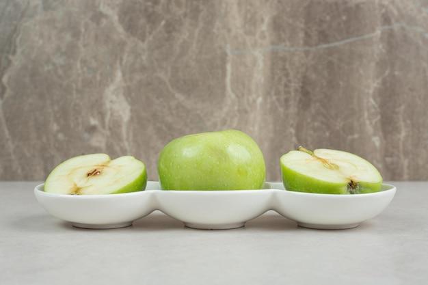 Całe i pół pokrojone zielone jabłka w białych miseczkach.