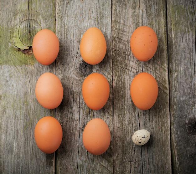 Całe jaja przepiórcze i kurze na małej żeliwnej patelni na powierzchni starej drewnianej tekstury