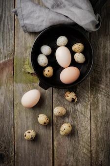 Całe jaja przepiórcze i kurze na małej żeliwnej patelni