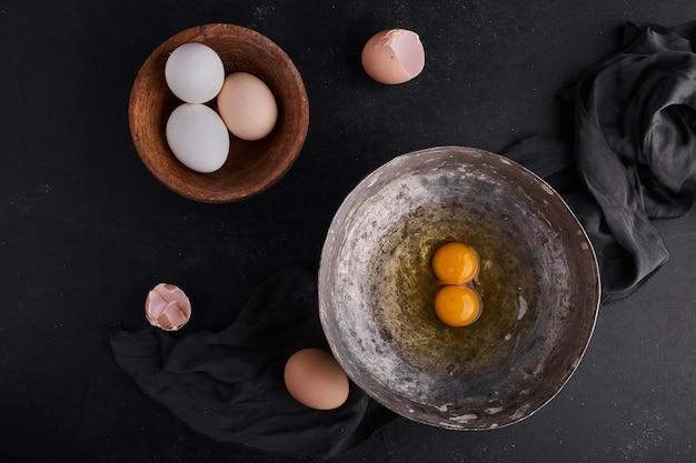 Całe jajka i żółtka na drewnianych i metalowych talerzach, widok z góry.