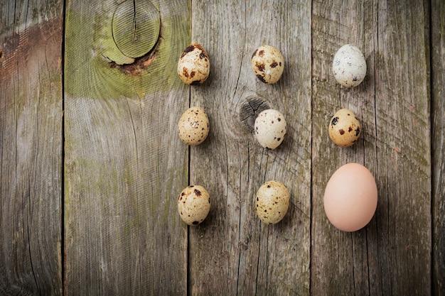 Całe jajka przepiórcze i kurze na małej żeliwnej patelni na tle starej drewnianej tekstury