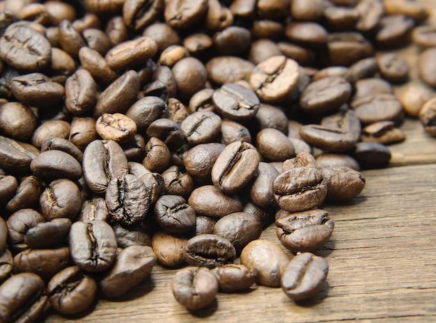 Całe kawowe fasole na drewnianym tle.