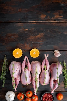 Całe mięso przepiórki z przyprawami, ziołami, warzywami, widok z góry, na ciemnym drewnianym stole