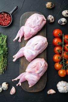 Całe mięso przepiórki z przyprawami, ziołami, warzywami, widok z góry, na czarnym stole