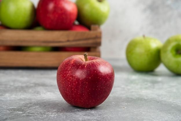 Całe mokre zielone i czerwone jabłka na drewnianej desce do krojenia.