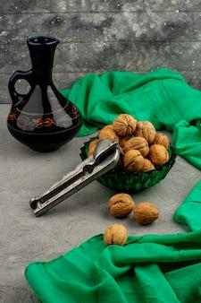 Całe orzechy brązowieją na zielonym talerzu i na zielonej chusteczce i szarej podłodze