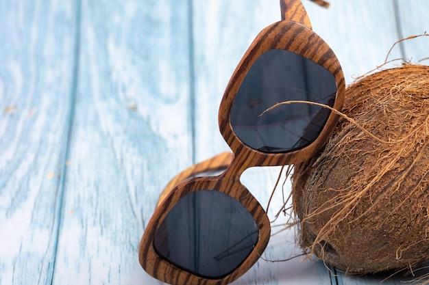 Całe orzechy kokosowe i drewniane szklanki na niebieskim drewnianym tle