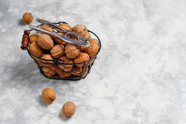 Całe orzechy włoskie w skorupkach w metalowym koszu spożywczym, jądra orzecha włoskiego. widok z góry na beton