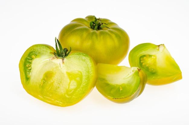 Całe owoce i plastry żółto-zielony kolor dojrzałych owoców pomidora, na białym tle. zdjęcie studyjne.