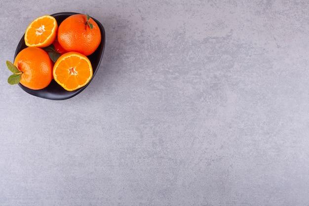 Całe pomarańczowe owoce z pokrojonymi w plasterki mandarynkami umieszczone w czarnej misce.