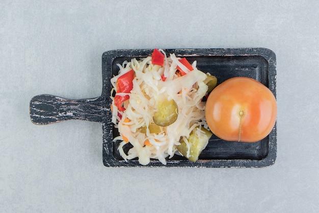 Całe pomidory i kiszona kapusta na desce