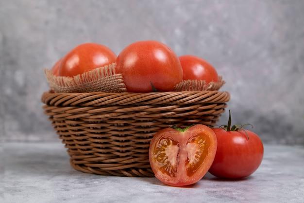 Całe soczyste czerwone pomidory w wiklinowym koszu umieszczonym na marmurze