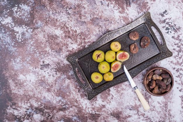 Całe, suche i pokrojone figi na metalowej tacy oraz w drewnianym kubku z nożem na bok.