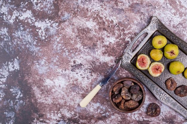 Całe, suszone i pokrojone figi na metalowej tacy iw drewnianym kubku.