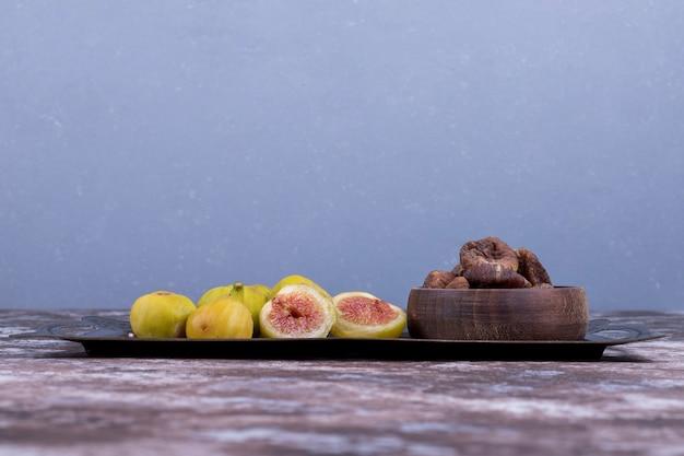 Całe, suszone i pokrojone figi na metalowej tacy oraz w drewnianym kubku na niebiesko.