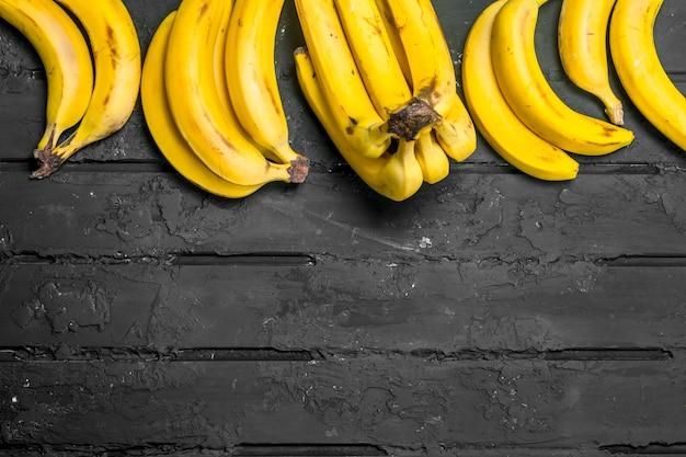 Całe świeże banany. na czarnym tle rustykalnym.