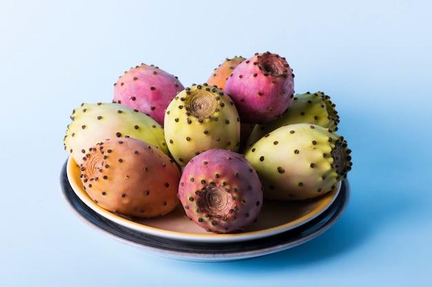 Całe świeże owoce opuncji w talerzu na pastelowym niebieskim tle