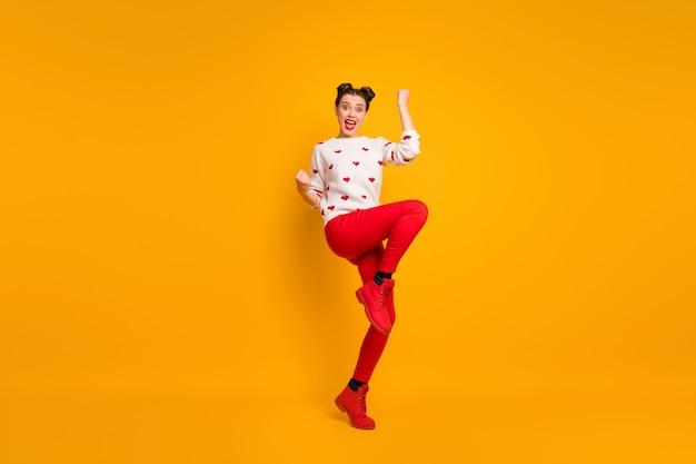Całe zdjęcie amora damy podnosi pięści jedną nogę świętując romantyczne zaproszenie na randkę, nosi wzór serca biały sweter czerwone spodnie obuwie