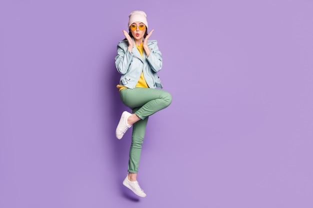 Całe zdjęcie ciała zdumionej śmiesznej dziewczyny skacze pod wrażeniem wspaniałych wiadomości nosić ubrania w stylu casual, buty gumowe odizolowane na żywym kolorze tła