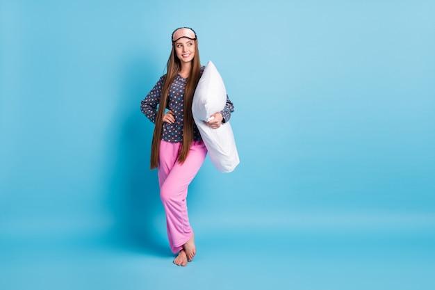 Całe zdjęcie wielkości ciała całkiem młoda dziewczyna wygląda na pustą przestrzeń przytrzymaj poduszkę boso decydując się iść łóżko lub oglądać telewizję nosić maskę kropkowaną koszulę piżamy bielizna nocna na białym tle jasny niebieski kolor tła