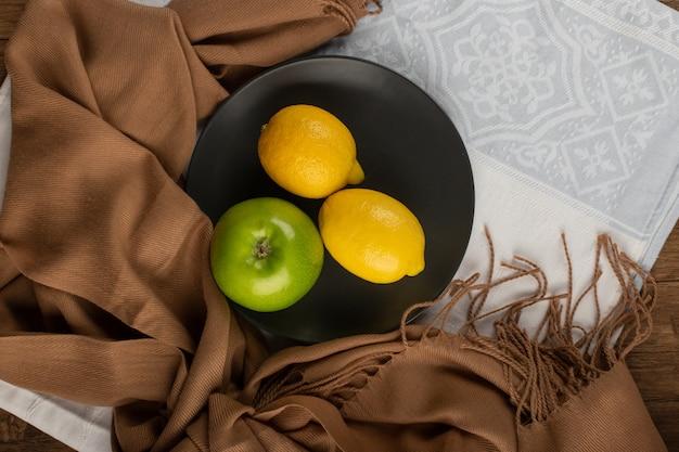 Całe zielone jabłka i cytryna na czarnym talerzu. widok z góry