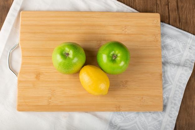 Całe zielone jabłka i cytryna na drewnianej desce. widok z góry