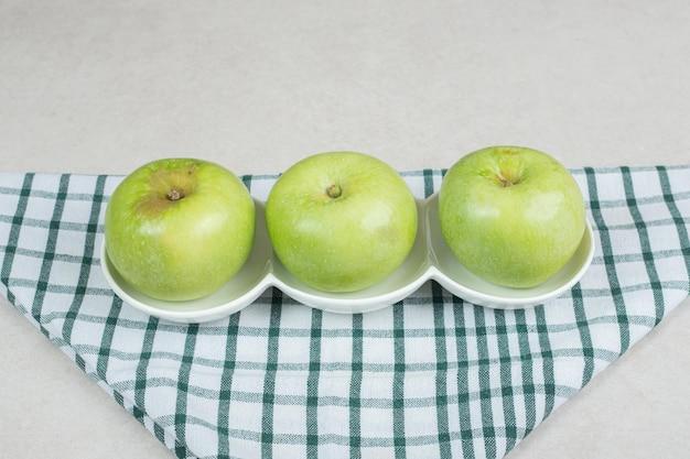 Całe zielone jabłka na białych talerzach z obrusem w paski