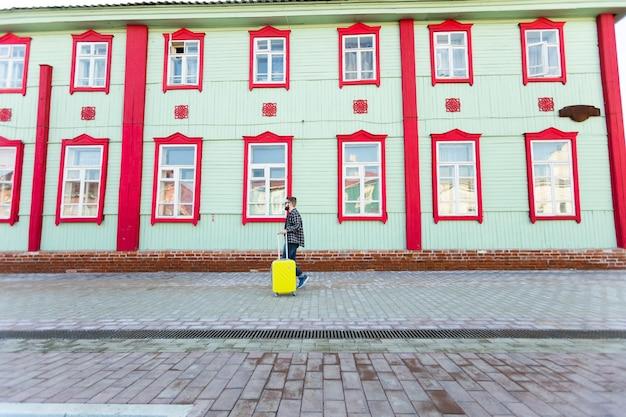Całego ciała boczny portret szczęśliwego człowieka podróży z walizką idącego wzdłuż budynku w mieście